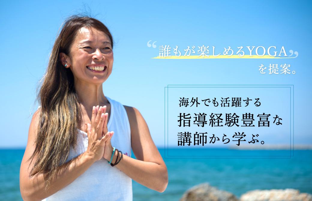 海の前で笑顔で手を合わせているクラタマイコ先生