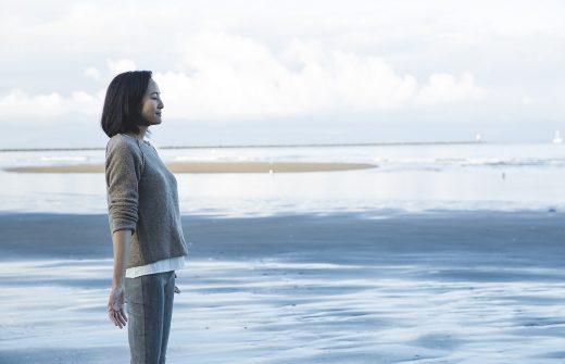 サントーシマ香先生が海の前で手を広げ目を閉じている