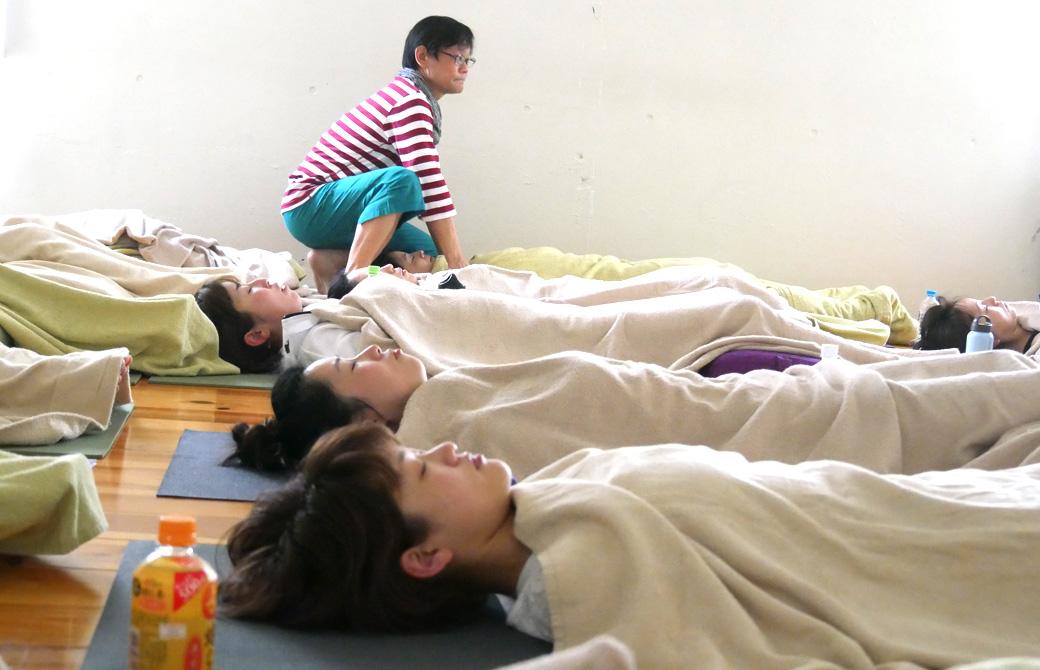 アナトミック骨盤ヨガワークショップの様子。大勢の生徒が毛布をかけて寝ている(シャバアサナ)講師(内田かつのり)がツボ押しをしている