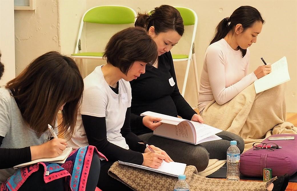 産後ヨガ指導者養成講座の生徒がテキストにメモをとっている