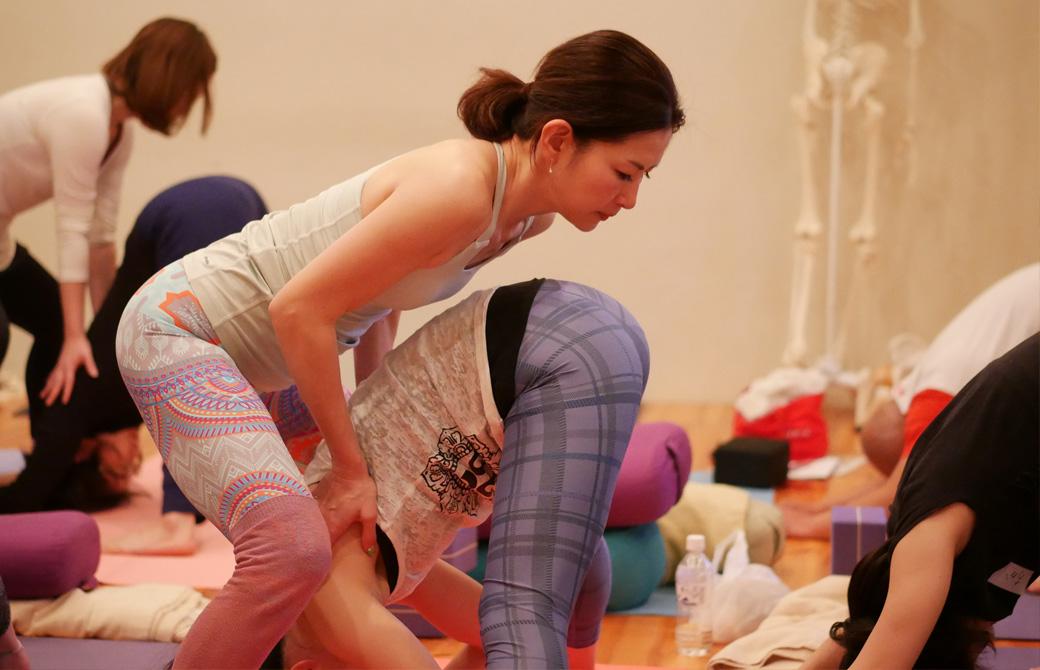 アナトミック骨盤ヨガ練習風景。女性が中腰の姿勢で腕を前方に伸ばして姿勢を正している様子。一人が立位前屈、もう一人が手を添えてアジャストしている様子