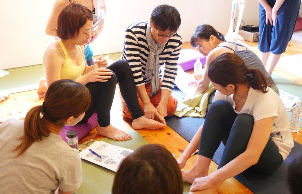 内田かつのり ヨガ解剖学:足裏アーチワークショップの様子。生徒さんの足を指さして説明する内田かつのり先生