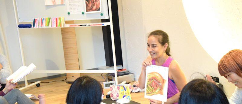 女性の体の仕組みを資料を見せながら笑顔で教えるキャシー