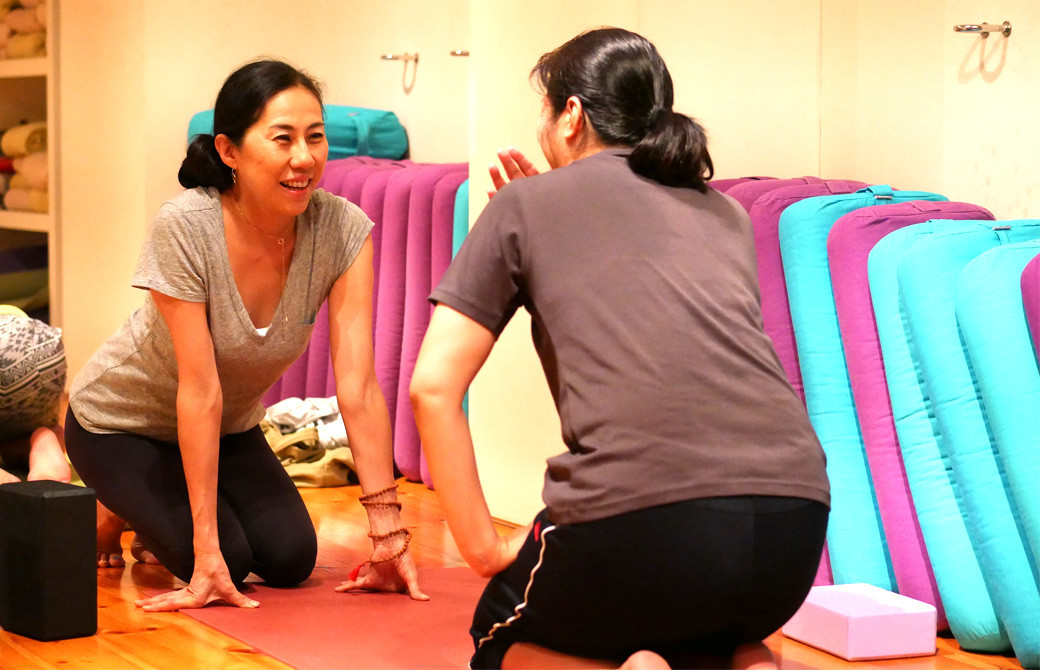 出口眞喜子先生の勉強会の風景。生徒さんに腰を落として話しかける出口先生