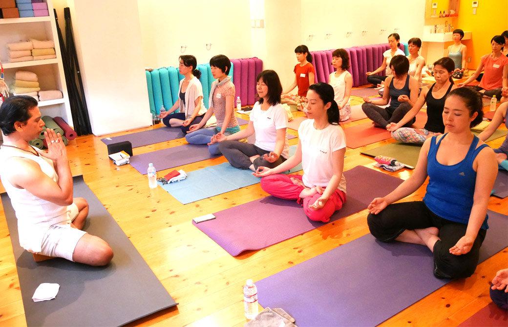 クリシュナグルジ先生の前にたくさんの生徒さんがマットを並べて座って瞑想している様子
