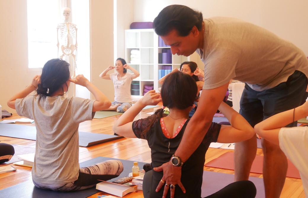 クリシュナ・グルジ先生のヨガセラピー指導者養成講座のクラス風景。座って呼吸法の練習をしている生徒さんの背中にグルジ先生が手を添えてアジャストしている様子。