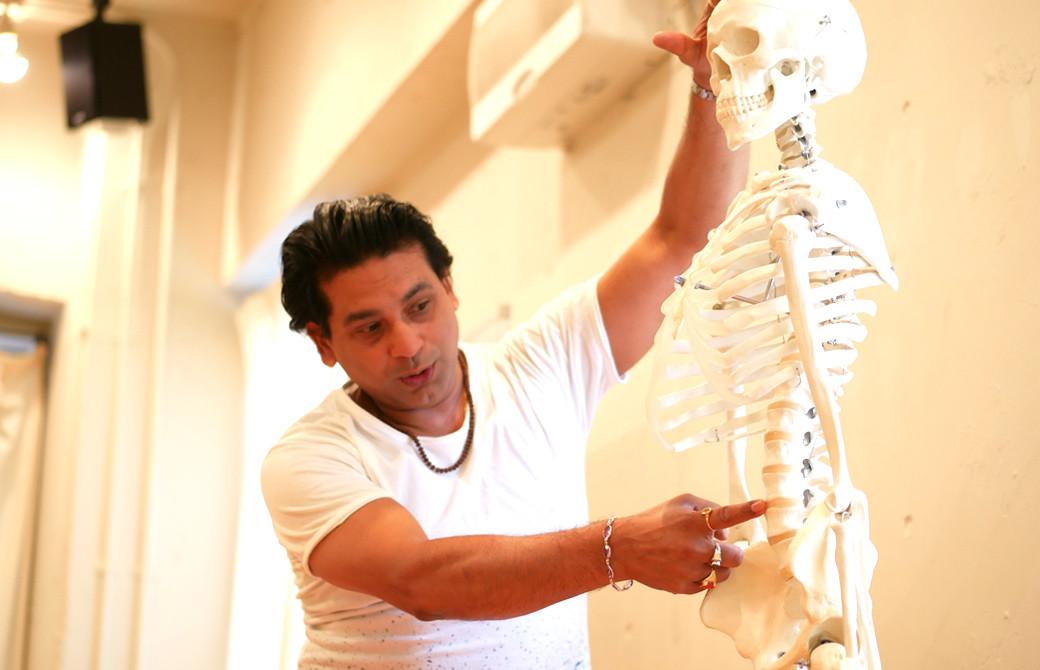 クリシュナ・グルジ先生のヨガセラピー指導者養成講座のクラス風景.グルジ先生が骨模型を使っ手説明している様子
