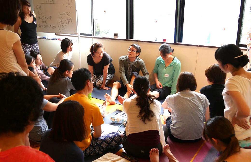 内田かつのりヨガ解剖学講座膝関節セラピーの様子。内田先生の話に大勢の生徒さんが集まって効いている