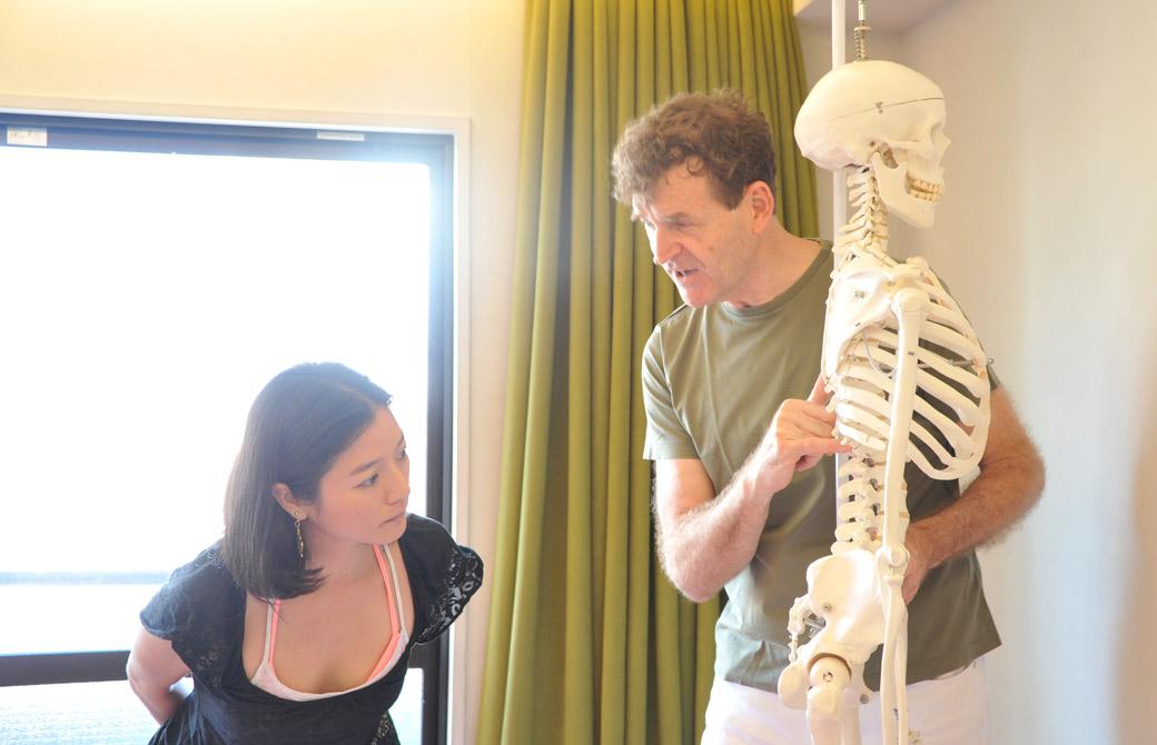 アレクサンダー・テクニーク講師ジェレミ―チャンス先生が骨模型を使用して説明している様子