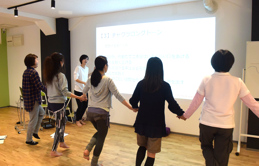 高橋淳子先生の声かけ、はないちもんめのように手をつないで横一列になった生徒さんが壁に向かって発声している様子