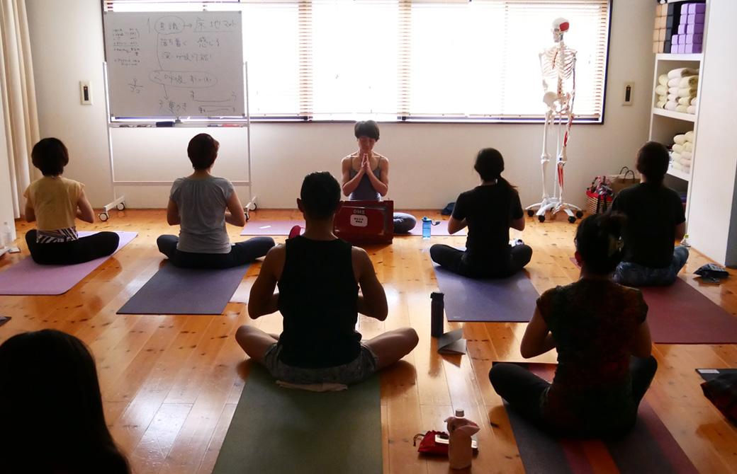 マキノカオリ先生の太陽礼拝マスター講座にて、カオリ先生と一緒に多くの生徒さんが蓮華座で胸の前で合唱し瞑想している様子