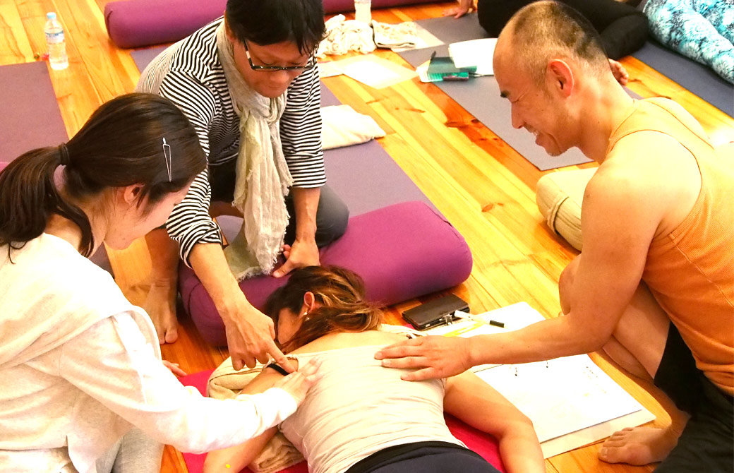 生徒の一人がうつ伏せに寝ている。肩甲骨周りを触って形を確認している様子