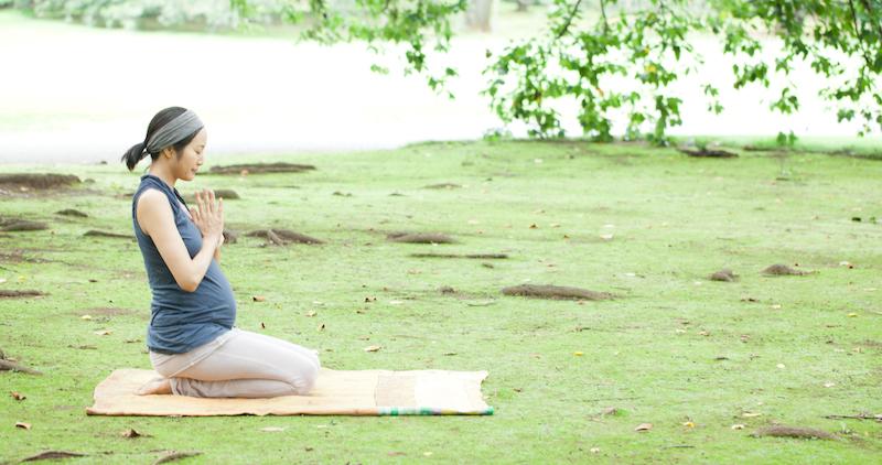 芝生の上で正座で合掌しているサントーシマ香先生