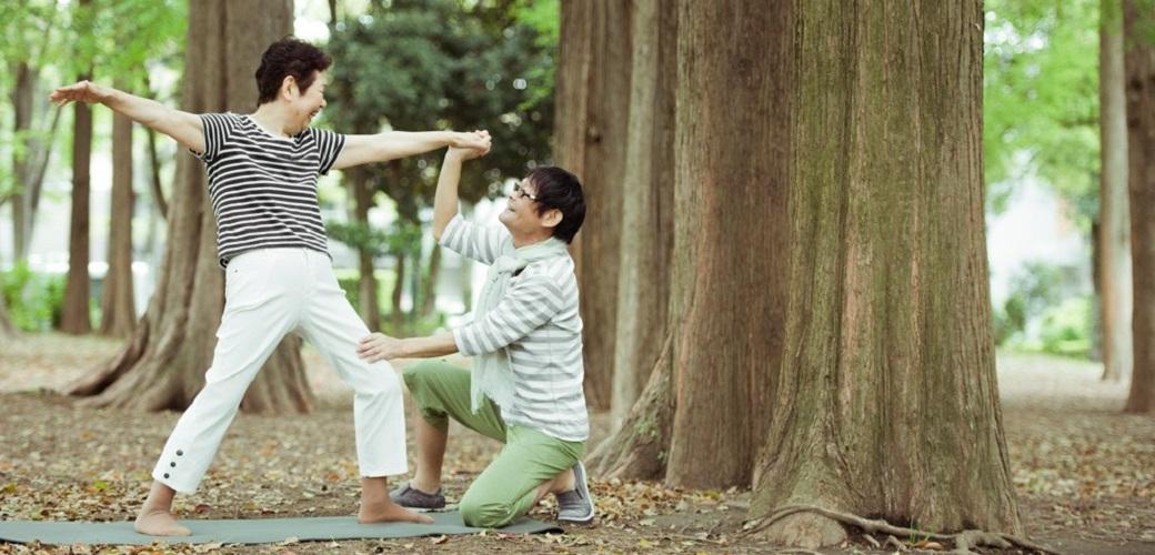 高齢の女性がヨガの戦士のポーズをしているのをアジャストする内田かつのり先生