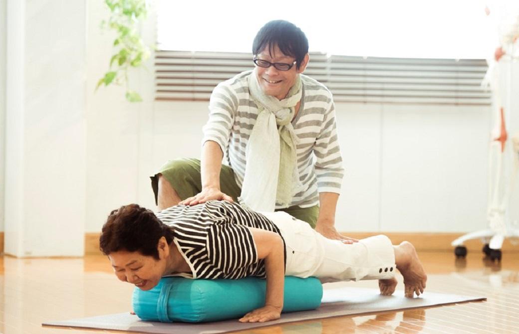 ボルスターの上にうつぶせになる高齢女性と、背中に手を添えている内田かつのり先生