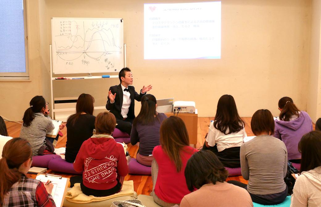 高尾美穂先生の女性のカラダの基礎知識:2.月経周期とそれに伴う症状の講座風景。プロジェクター画像を指さして説明している様子