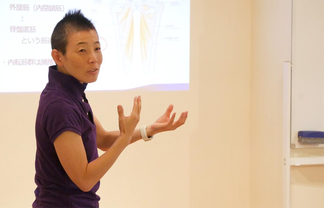 高尾美穂先生がプロジェクターの映像の前で手振りを使いながら説明している様子