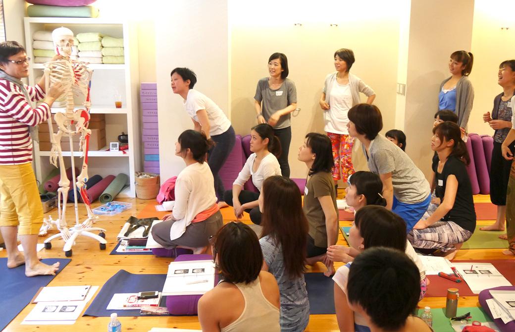 ヨガ解剖学ティーチャーズトレーニング講座風景。講師(内田かつのり)が骨模型を使用して説明しているのを大勢の生徒が囲む