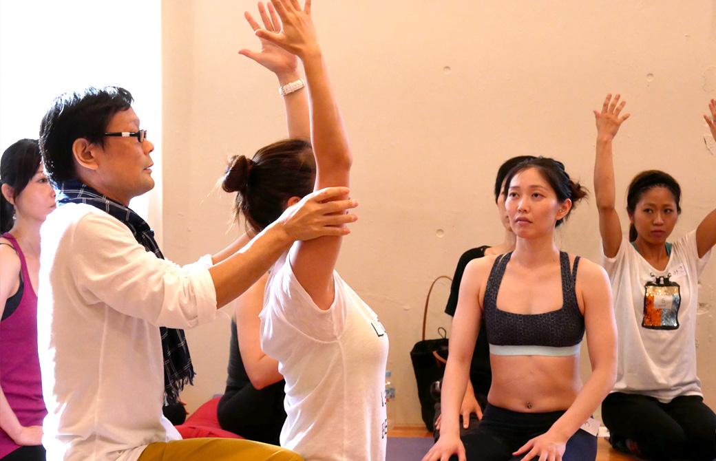 アナトミックアジャストメント講座風景。ヨガ講師(内田かつのり)が生徒二アジャストをして、その説明を周りの生徒がきいている様子