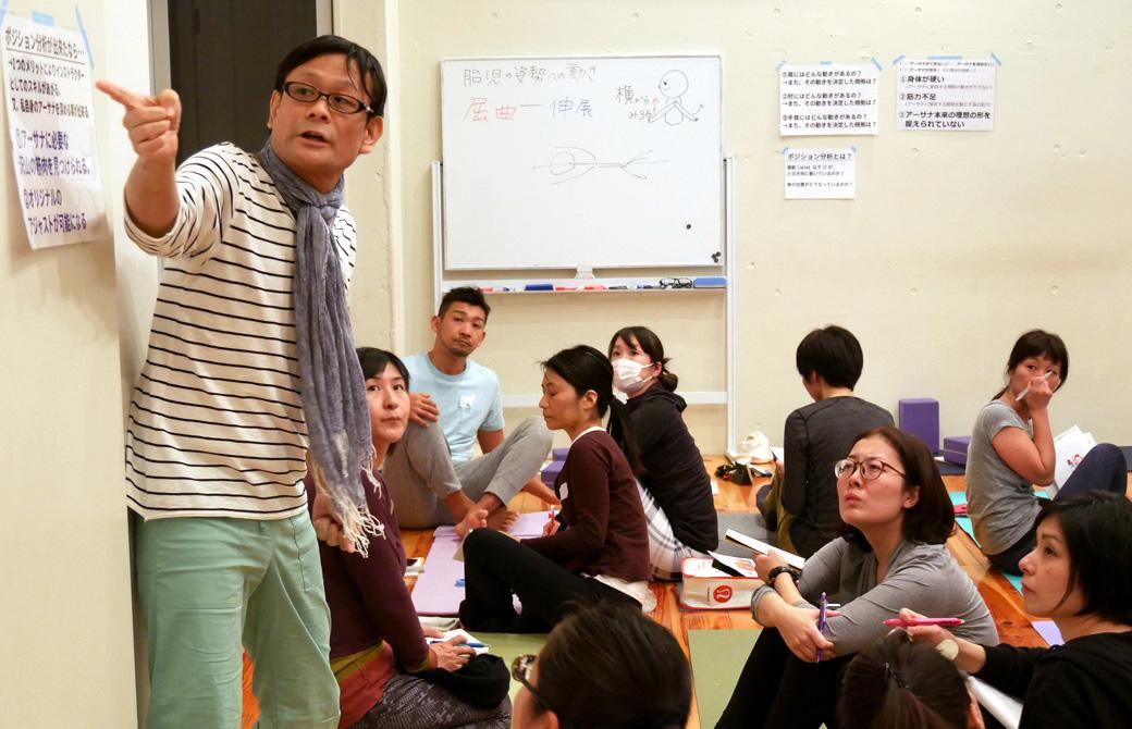 ヨガ解剖学講座基礎編の講座風景。講師(内田かつのり)が壁に貼った資料を指差しながら説明し、それを真剣にきいている生徒の様子