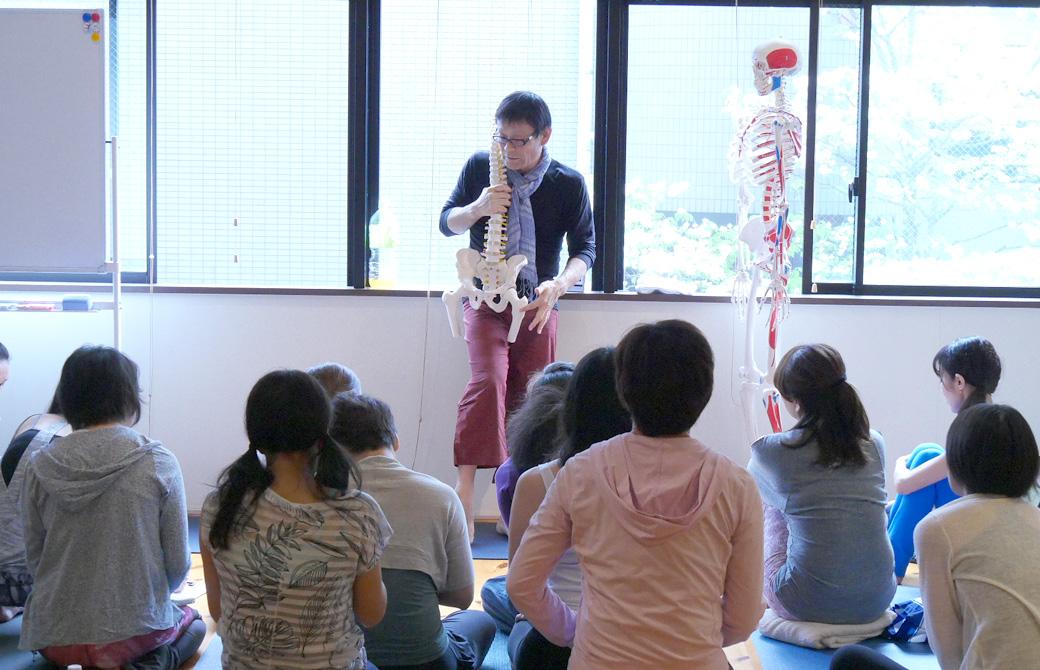 ヨガ解剖学講座怪我をしないさせない講座風景。講師(内田かつのり)が骨模型を使用して説明しているのを大勢の生徒が囲む