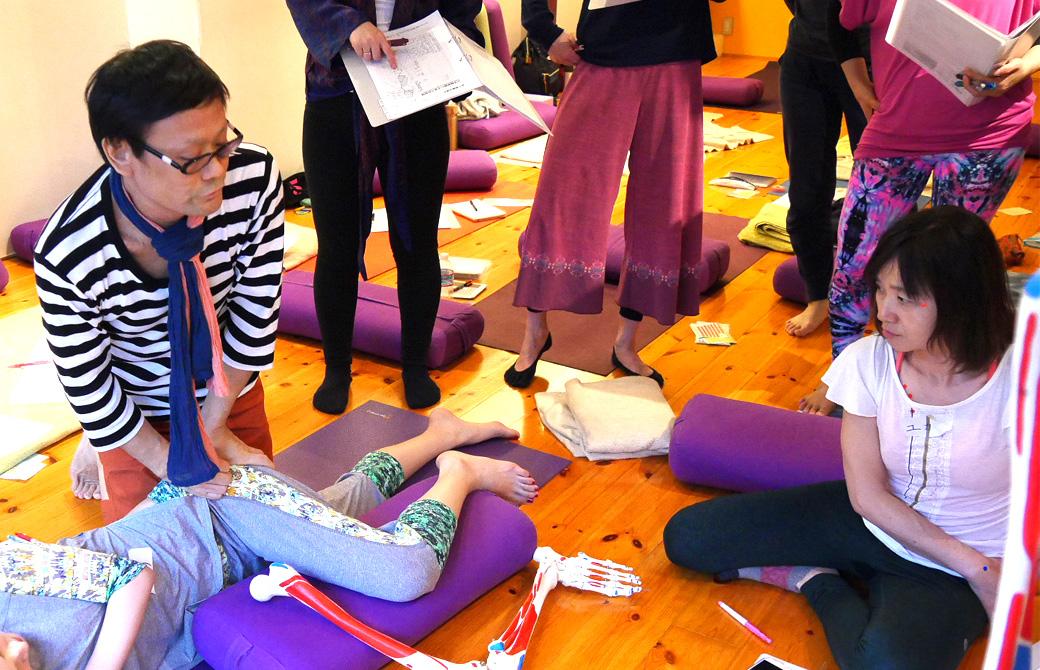 経絡(けいらく)基礎を学ぶ講座(3日間)の講座風景。講師(内田かつのり)が寝ている生徒の脚の横に骨模型を同じ状態で置き、ツボの位置を説明している様子