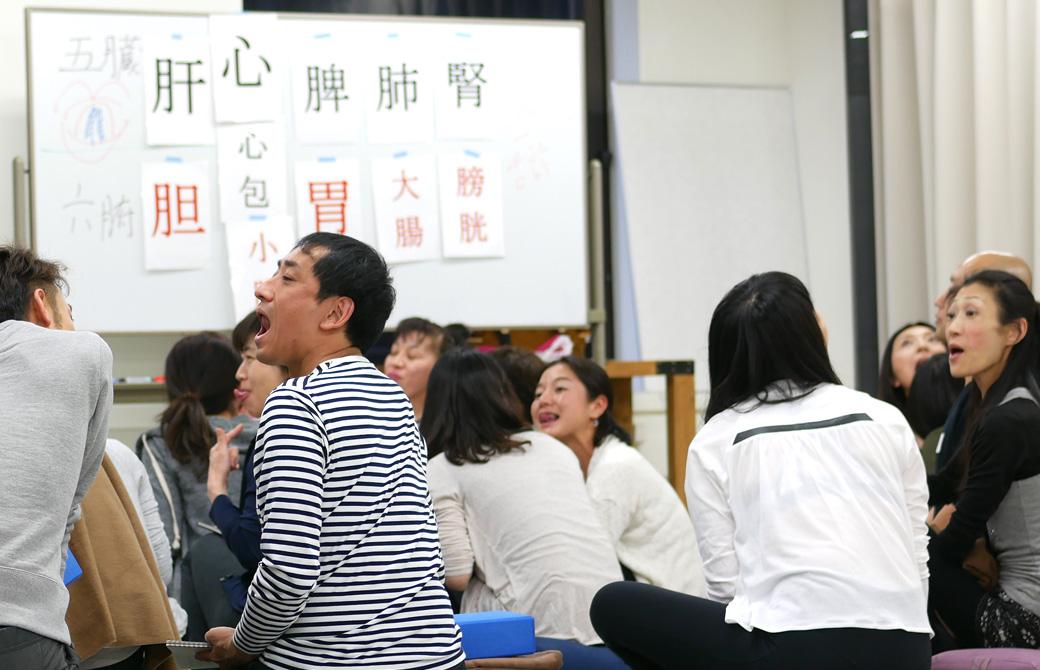 経絡ワークショップの講座風景。大勢の生徒さんがお互いに舌の裏側を見せ合いっこしている様子