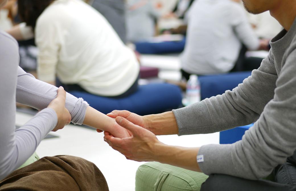 経絡ワークショップの講座風景。女性の腕をとり男性が手首のツボを押している様子