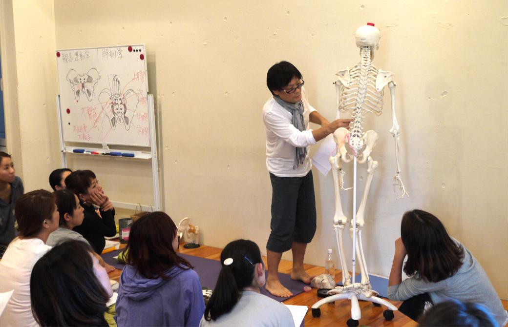 ヨガ解剖学骨盤セラピーの講座風景。講師内田かつのりが全身骨模型で説明している様子