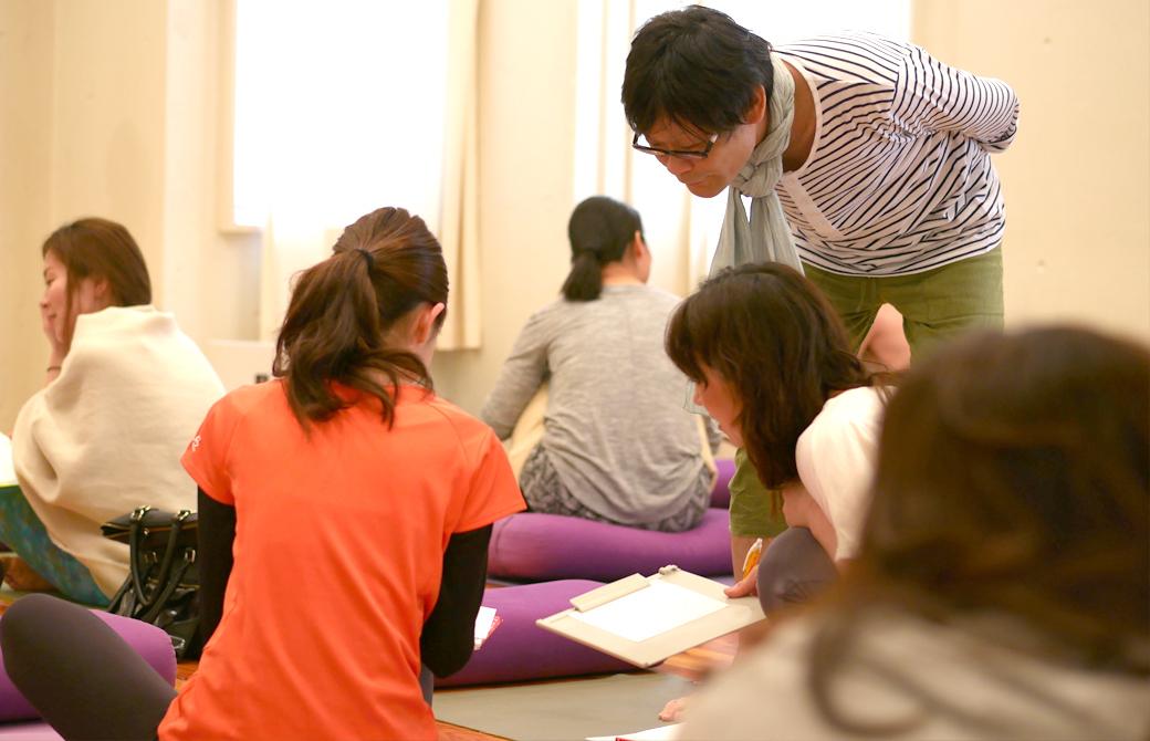ヨガ×東洋医学の講座風景。講師内田かつのりがグループワーク中の生徒をのぞき込んで見守っている。