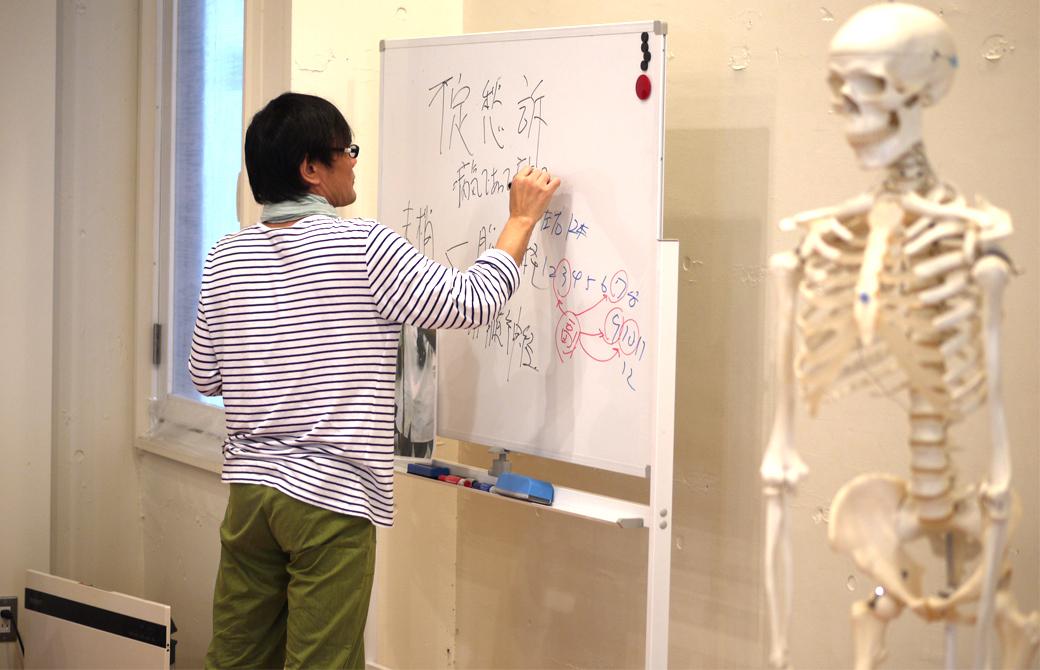 ヨガ×東洋医学の講座風景。講師内田かつのりがホワイトボードに板書している。