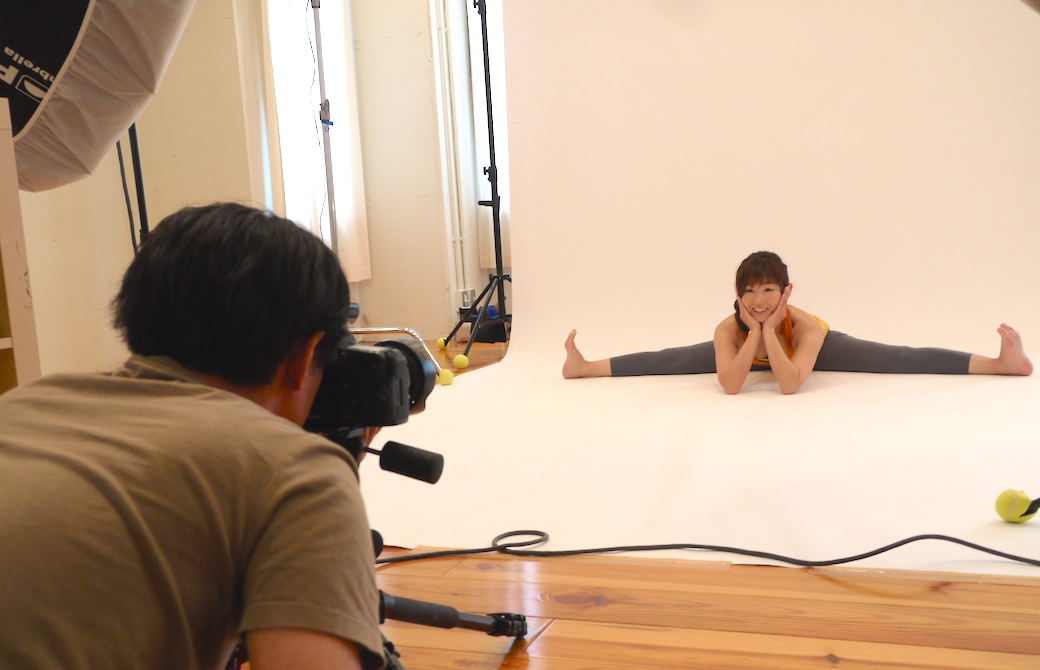 開脚で柔軟性をアピールする写真を撮影している女性