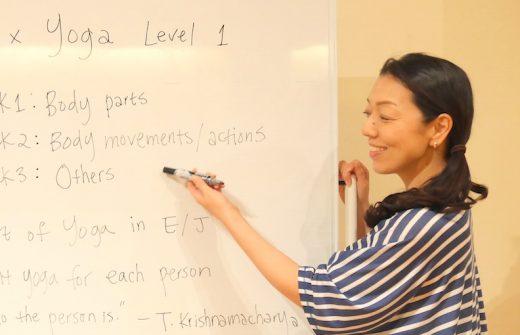 ホワイトボード前でヨガ英語の表現方法について説明している川原朋子先生