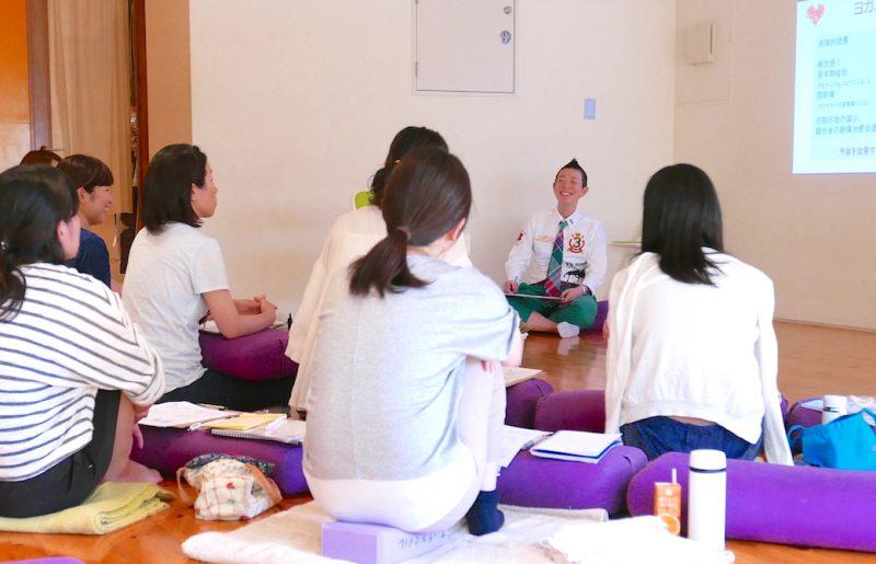 高尾先生がプロジェクターの前で生徒さんに向かって笑顔でお話している