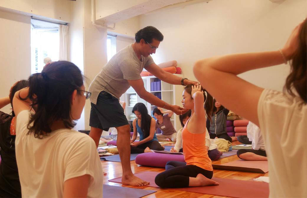 クリシュナ・グルジヨガ指導者養成講座ヨガセラピーの講座風景。講師グルジが座っている生徒の顔を上下から挟み込むようにして手を添えて、首を鍛える運動のアジャストをしている