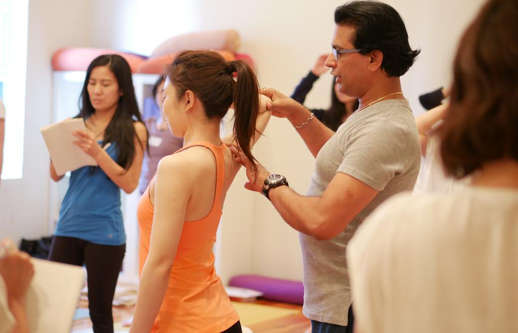 クリシュナ・グルジヨガ指導者養成講座ヨガセラピーの講座風景。講師グルジが生徒の背後から腕に手を添えて、説明している