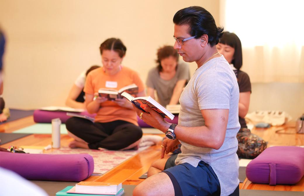 クリシュナ・グルジヨガ指導者養成講座ヨガセラピーの講座風景。講師グルジと生徒の皆さんが参考図書に目を落としている様子