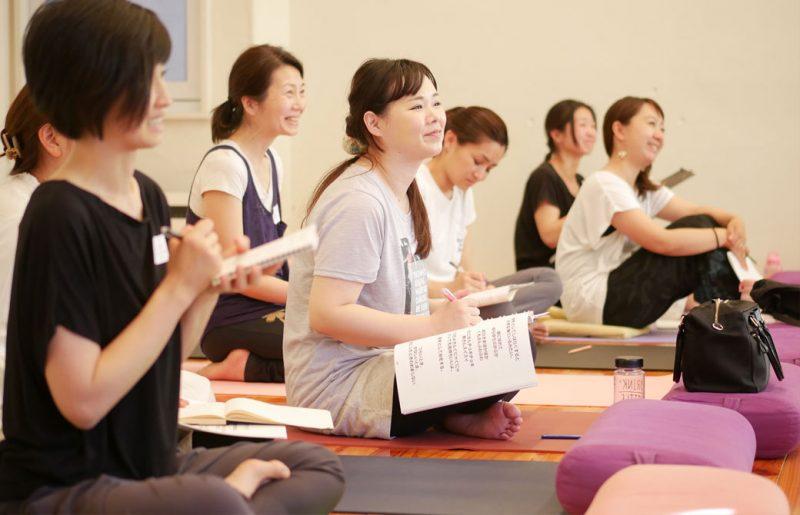 片岡まり子先生のキッズヨガワークショップ風景。生徒が笑顔で講師の話をきいている様子