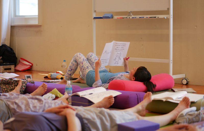 片岡まり子先生のキッズヨガワークショップ風景。寝っ転がって絵本を読み聞かせる片岡先生