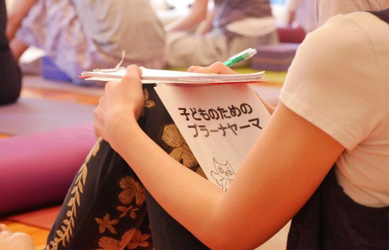 片岡まり子先生のキッズヨガワークショップ風景。絵本を膝の上に乗せる生徒