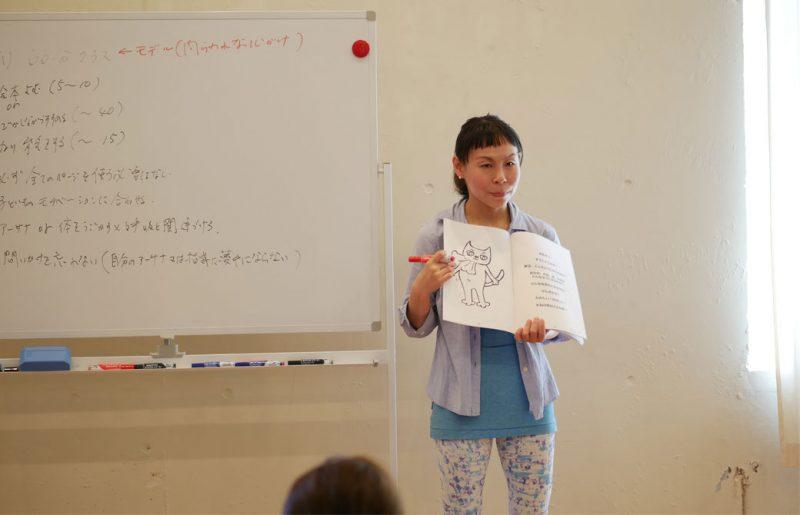 片岡まり子先生のキッズヨガワークショップ風景。絵本を持って説明する片岡先生