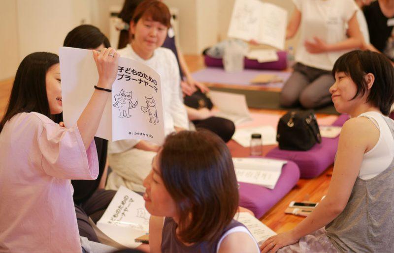片岡まり子先生のキッズヨガワークショップ風景。生徒が読み聞かせのワークをしている様子