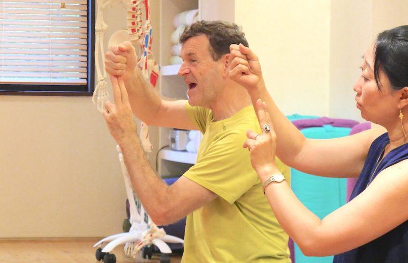 グーの手で頭、チョキの手で脊椎を表現して説明してりるジェレミー先生