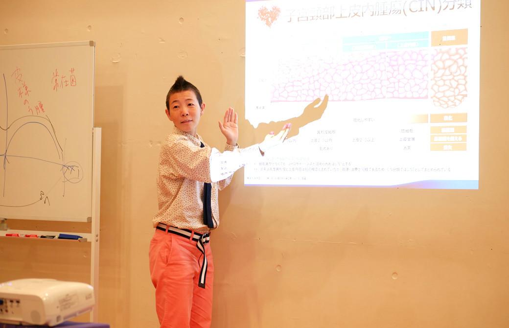 高尾美穂先生が投影された表を指さして説明している様子