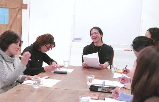 和也先生がテキストを持ちながら笑顔で話をしている
