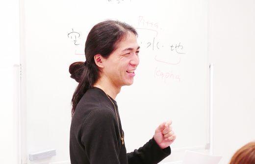 ホワイトボードの前で笑顔で講義している和也先生