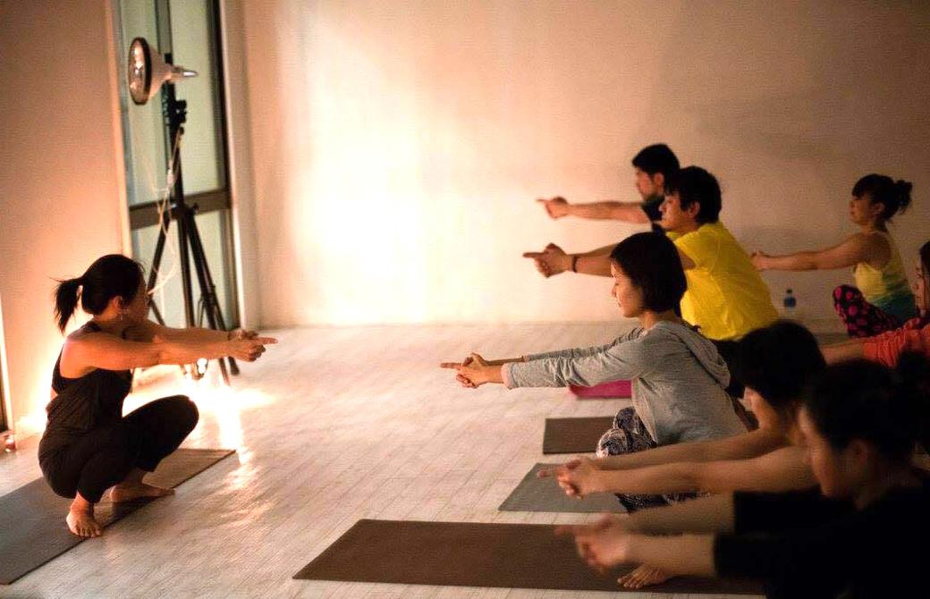 講師Maikoと生徒さんのクンダリーニヨガクラスの様子。中腰で、人差し指を伸ばしてまっすくうでを前に伸ばしている様子