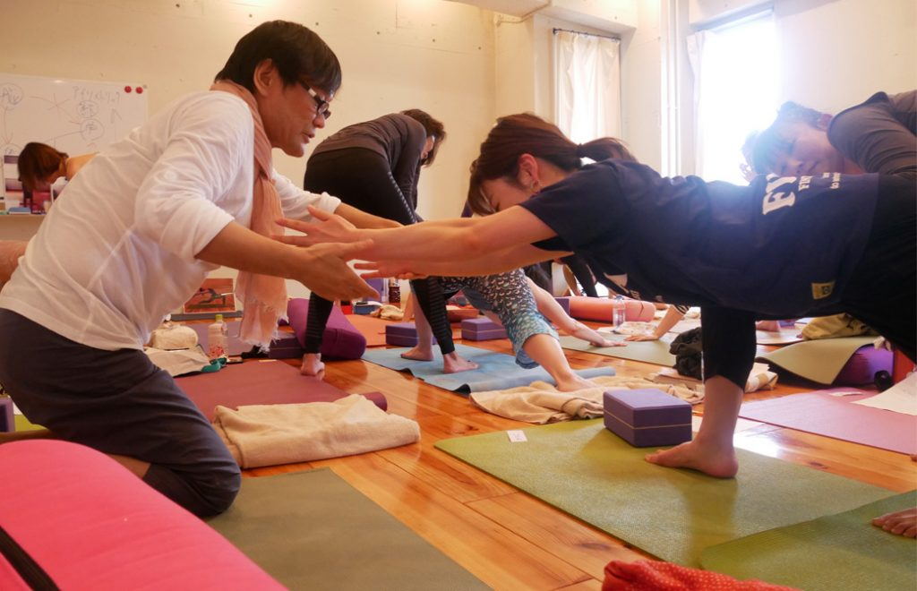 アナトミック骨盤ヨガ®ワークショップの講座風景。内田かつのり先生が生徒さんの手をとってアジャストしているところ