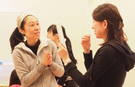 篠原もとこ先生が鏡を持った生徒さんにマンツーマンで教えている