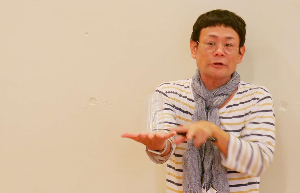 コップを手に乗せて、安定について説明する内田かつのり先生